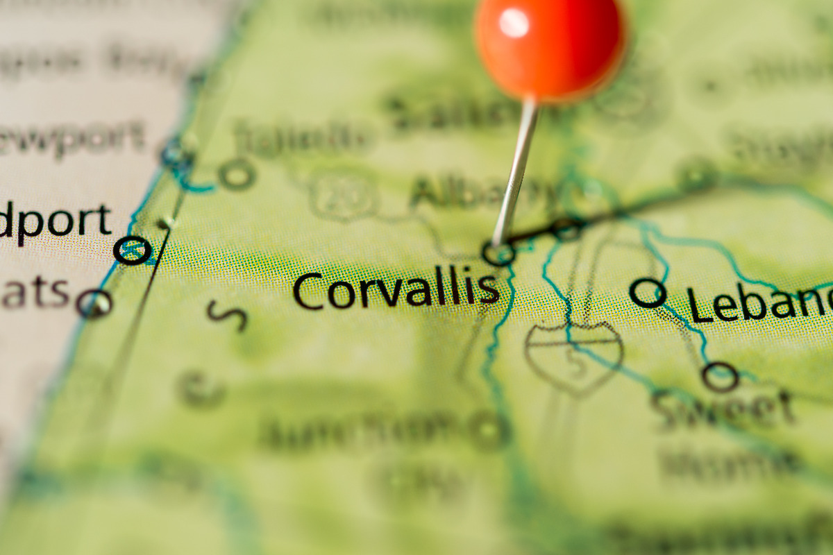Extreme close-up of a state map centered on Corvallis, Oregon, with a red push pin marking Corvallis' location