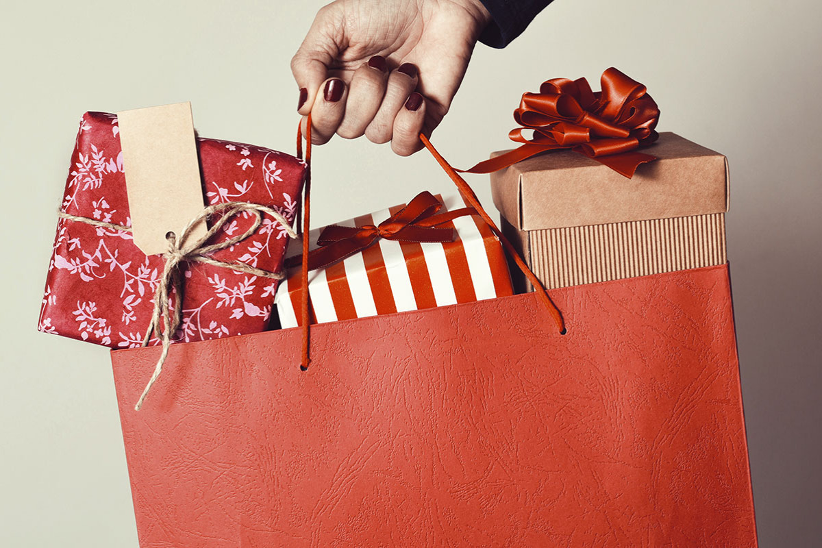 A red paper bag full of wrapped holiday gifts.