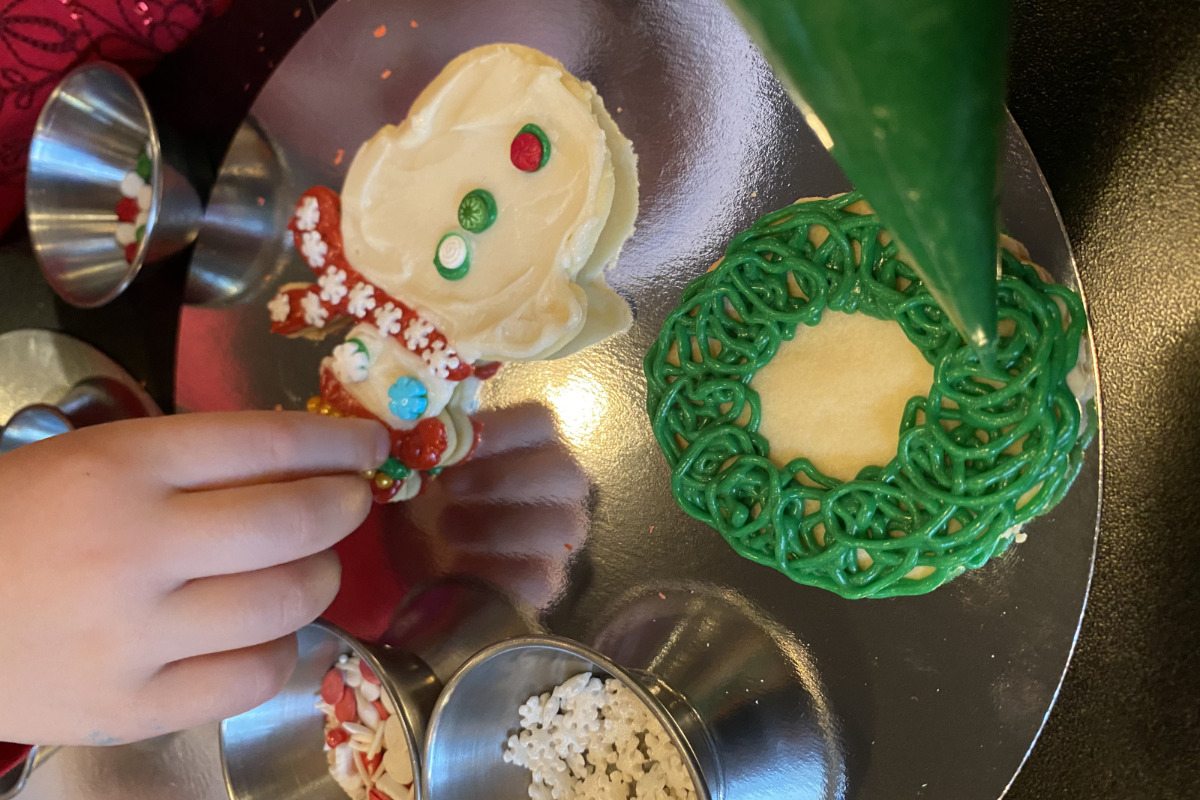 Brass Monkey's cookie decorating kit, showing a decorated snowman cookie, a wreath cookie, and sprinkles.