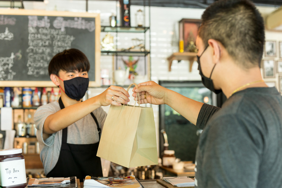 Get takeout - A masked server hands a takeout bag across a counter to a masked customer