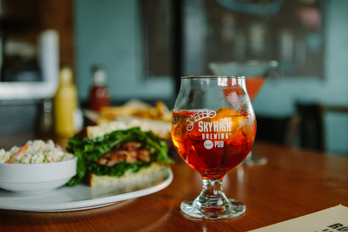 Sky High Brewing & Pub, Corvallis, Oregon - A Sky High logo glass of beer with a plate of food on a table inside Sky High Brewery