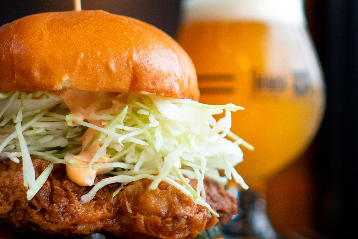 Block 15 Brewing, Corvallis, Oregon - The buttermilk fried chicken sandwich, with a glass of beer in the background.