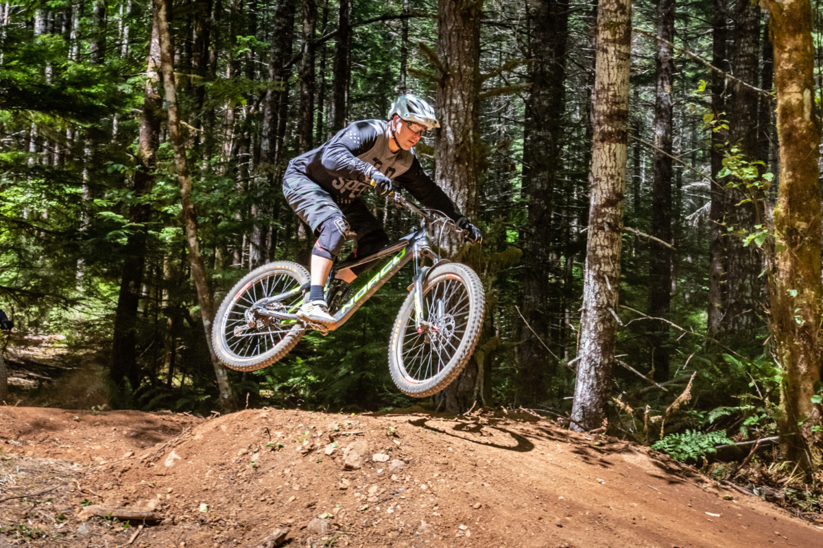 Team Dirt, mountain biking at Alsea Falls Recreation Area, by Reed Lane Photography - A man in mountain biking gear rides a trail at Alsea Falls, jumping a berm on a dirt trail, in the foreground, wit