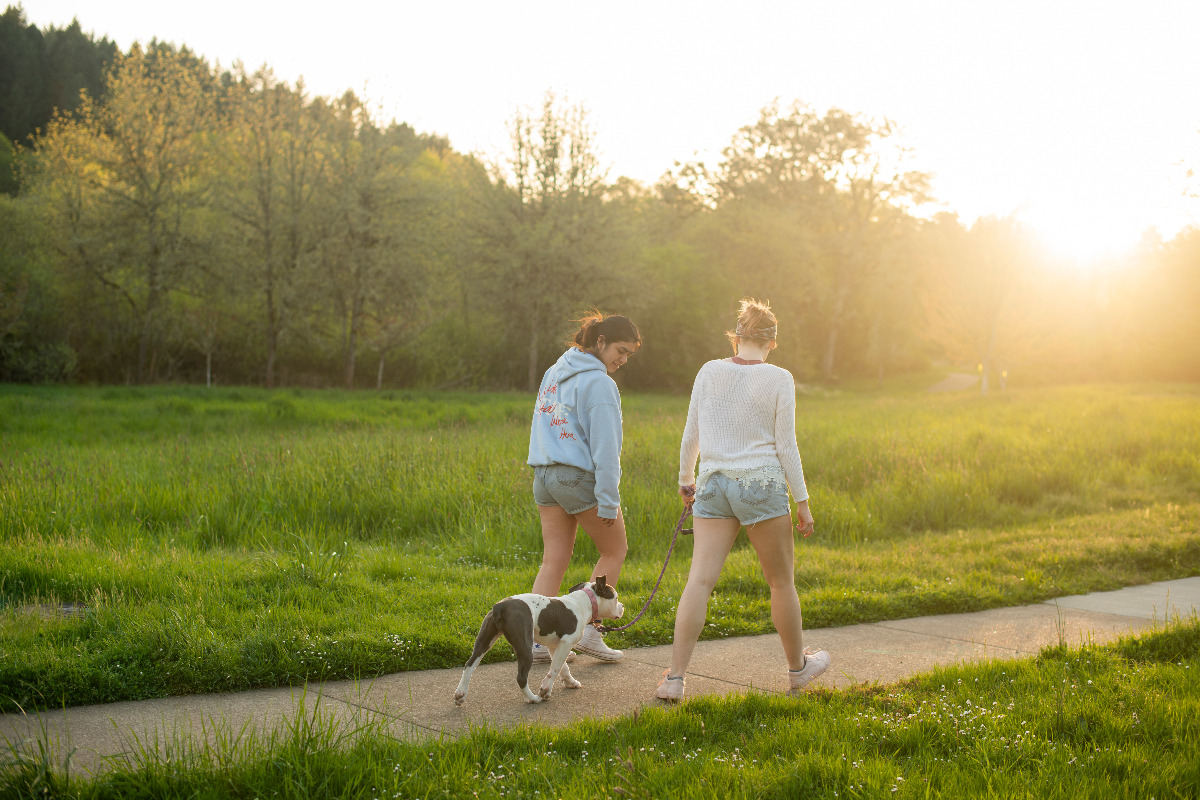 Two women hiking with their dog through Martin Luthor King, Jr. Park in Corvallis, Oregon, during a spring evening, by Isabella Medina