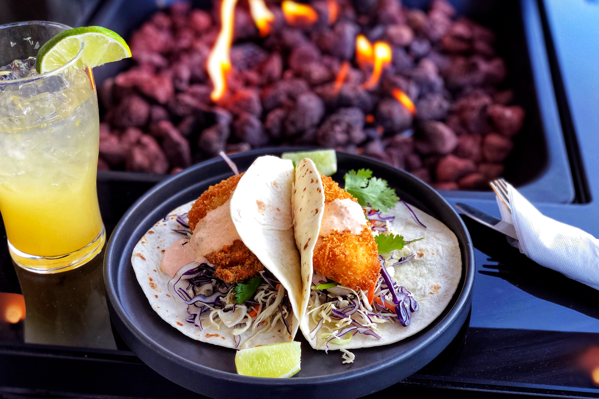 McMenamins, Corvallis, Oregon - Fish tacos on a plate blanaced on an outdoor table with an inserted fire bowl