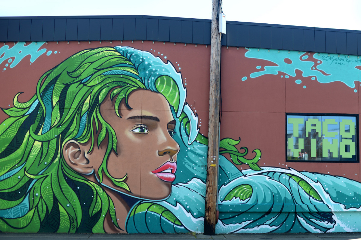 Mural in Corvallis, Oregon showing a woman with green and blue hair that looks like waves and leaves.