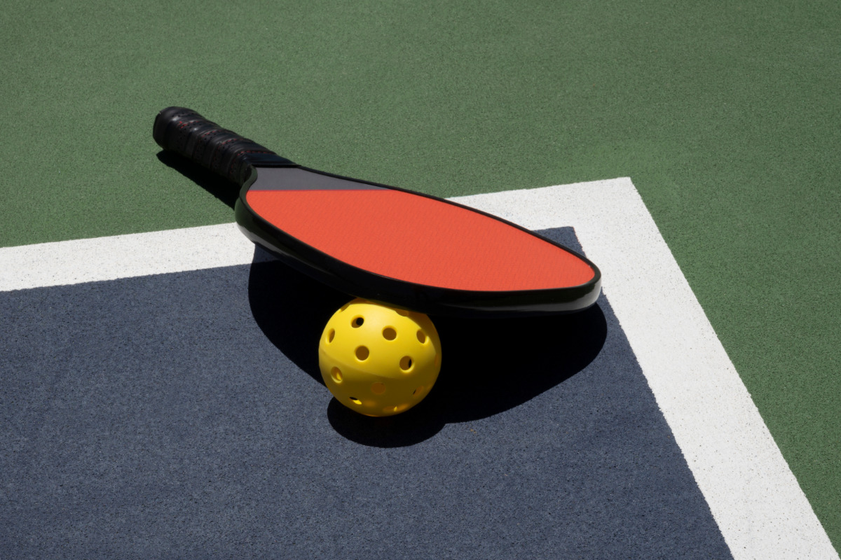 Pickleball paddle and ball on a court