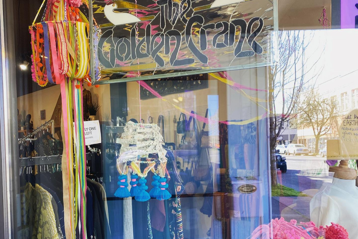 The Golden Crane, Corvallis, Oregon - The front of a resale boutique showing the store sign and through the window, clothes and accessories - via Facebook