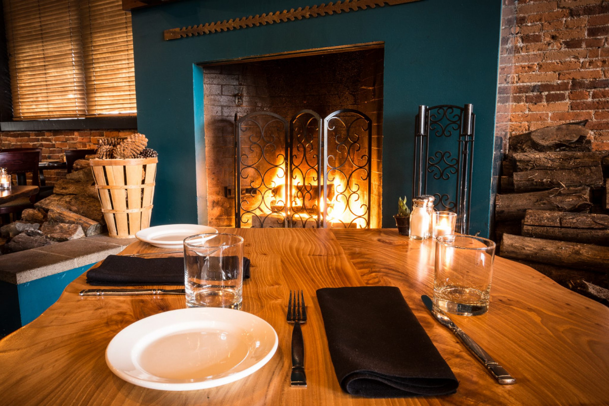 Sybaris Bistro, Albany, Oregon - A glossy wooden table, set for dinner, by the fireplace - Image via Facebook