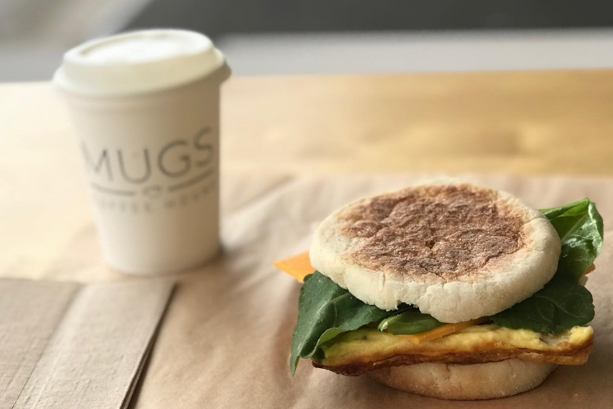 Mugs Coffee House, Lebanon, Oregon - A paper logo cup with coffee with an egg snadwich on a table in the coffee shop - Image via Facebook